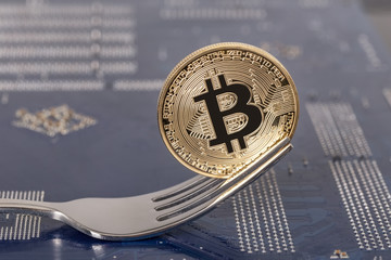 Coin bitcoin on the motherboard in the fork. Closeup