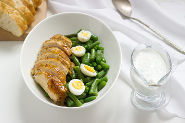 Roasted chicken breasts served with fried egg and boiled green beans.