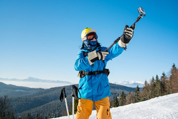 Professional skier in colorful winter clothing taking a selfie with action camera on selfie stick posing on top of a mountain copyspace ski resort recreation travelling tourism vacation adrenaline