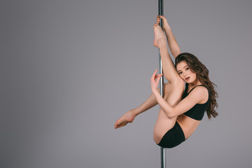 Obraz sensual young female dancer exercising with pole and looking at camera on grey - fototapety do salonu