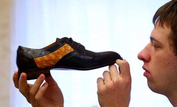Shoemaker Koppitz works on a handmade shoe with parrot fish leather in workshop in Grafing