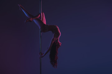 beautiful sensual flexible girl exercising with pole on blue Wall mural