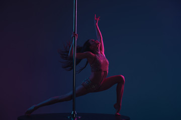 attractive sporty girl dancing with pole on blue