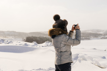 woman in winter hat photographing snow-covered field