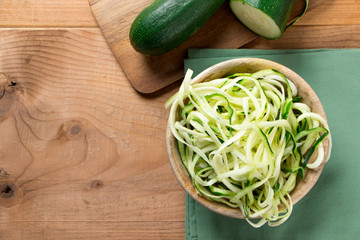 Raw zucchini noodles on a rustic background