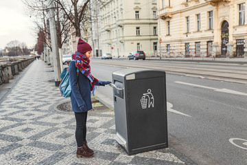 Portrait of a young woman throwing garbage in recycling bin at city street