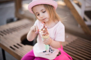 blonde little girl sitting with ice cream