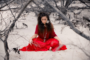 Beautiful young woman in red dress sitting on sand on the beach. Witchcraft conceptual image