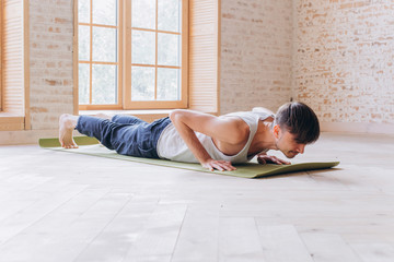 Relaxed young man doing yoga and meditating in studio