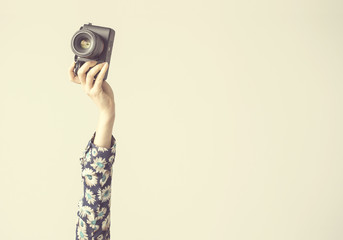 Wall Mural - Female, arm lifted up and holding camera, isolated background