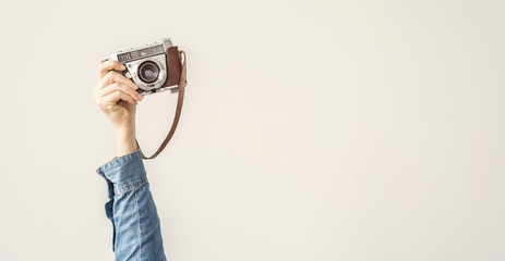 Wall Mural - Raised up, arm holding vintage camera isolated background