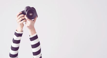 Young female raised arm up holding camera, isolated background