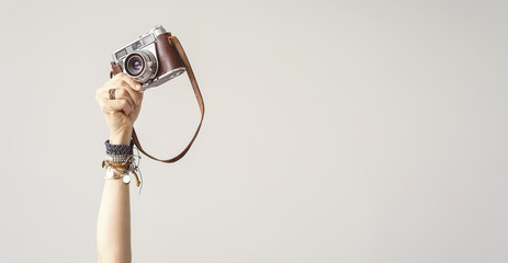 Wall Mural - Woman arm raised up holding camera isolated background