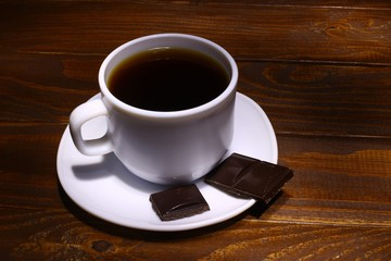 Coffee in a white pot and chocolate on a wooden background