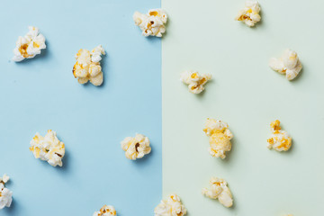 The popcorn in paper cup on green and blue background.