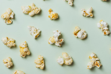 The popcorn in paper cup on green background.
