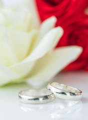 Red rose and wedding ring on white