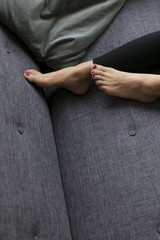 Feet of woman lying on couch at home