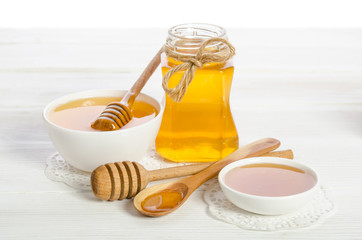 honey in a spoon, a jar and a bowl on wooden table