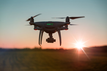 Picture of flying white drone camera during sunset