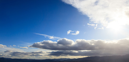 Blue sky background with scattered clouds over mountains silhouette. Aerial, panoramic photo banner