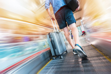Traveler man holding a suitcase on a speedwalk in airport
