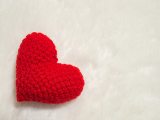 handmade red yarn heart on white wool. the red heart on the left of picture and background copy space for text. Valentines day, love concept and love background