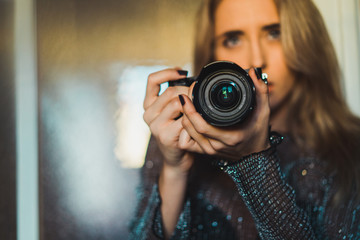 Young blonde woman with camera