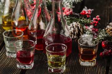 Assorted alcoholic cordials in glasses and decanters with Christmas decorations on dark wood background