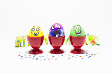 Group of colorful painted Easter eggs with funny cartoon style faces in red plastic egg cups and colorful confetti with paper streamer on white background