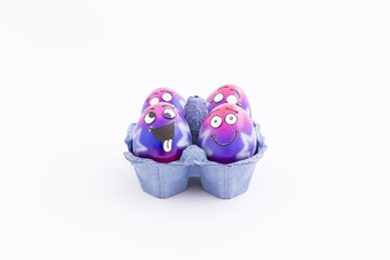 Group of colorful painted Easter eggs with funny cartoon style faces in a light blue egg box on white background