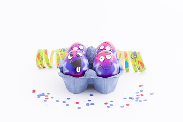 Group of colorful painted Easter eggs with funny cartoon style faces in a light blue egg box, colorful confetti and paper streamer on white background
