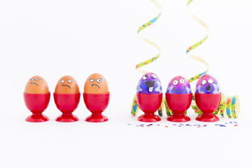 Group of colorful painted Easter eggs with funny cartoon style faces, confetti and paper streamers and group of grumpy looking brown eggs in red plastic egg cups on white background