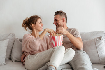 Portrait of a happy young couple eating popcorn