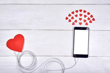 Mobile cellphone with blank screen charging with red paper heart on white wooden background, copy space. Mockup template for Valentines Day. Love, technology concept. Top view, flat lay