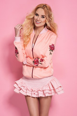 Fashion photo of a beautiful elegant young woman in a pretty skirt and bomber with flowers holding handbag posing over pink background. Fashion photo