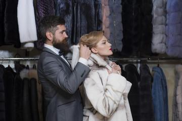 Customer with beard and woman buy furry coat.
