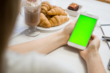 smartphone in the hands of a green screen in a cafe, smart phone with chroma key green screen on white background, new technology concept close up