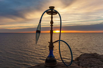 Hookah against the sky, water and sunset standing on the sand. Hookah on the background of the water of the sunset.