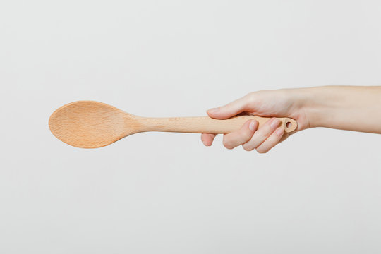 Close up of female hand horizontal holding wooden kitchen spoon for stirring and tasting food in the kitchen isolated on white background. Kitchen utensils concept. Copy space for advertisement.