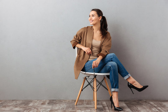Portrait of a cheery asian woman sitting on a chair