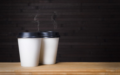two disposable white glasses of smoking coffee on a black wooden background