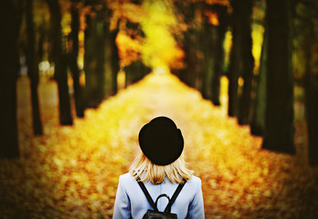 A girl in a black hat with a backpack on the avenue of the autumn park with her back