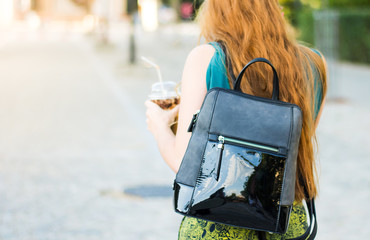 Girl walking on the street with coffee to go
