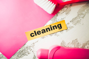 Cleaning, Laundry, Housekeeping concept concrete background with pink cleaning tools and Cleaning inscription, top view, copy space.