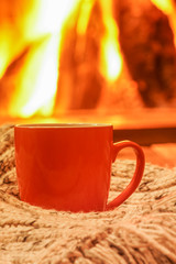 Orange mug for tea or coffee; wool things near cozy fireplace; winter vacations.;
