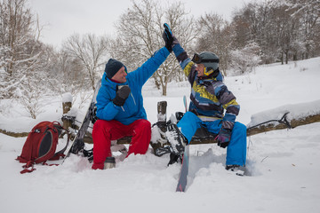 Cheerful snowboarders are drinking coffee after successful freeride