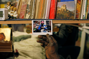 Samuel Pieta, 33, shows a picture of him holding his cat in his apartment room in one of the four occupied buildings by migrants of the former Olympic village in Turin