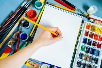 woman painter paints colorful paints on a white sheet of paper