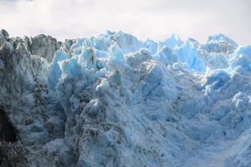 ostre krawędzie czoła lodowca w kolorze biało niebieskim w zbliżeniu z zachmurzonym niebem w tle